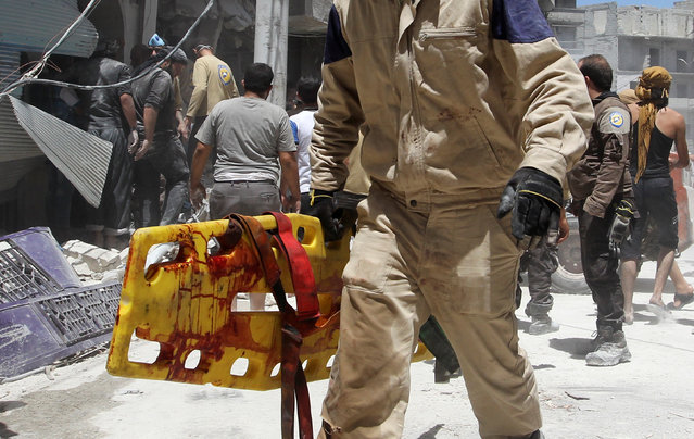 A civil defense member holds a blood-stained stretcher at a site hit by airstrikes in the rebel-controlled town of Ariha in Idlib province, Syria July 13, 2016. (Photo by Ammar Abdullah/Reuters)