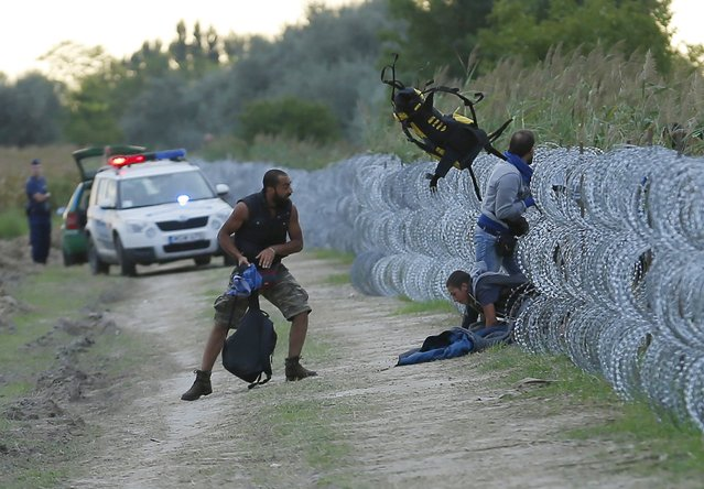 Hungarian police positioned nearby watch as Syrian migrants climb under a fence to enter Hungary at the Hungarian-Serbian border near Roszke, Hungary August 26, 2015. Hungary's government has started to construct a 175-km-long (110-mile-long) fence on its border with Serbia in order to halt a massive flow of migrants who enter the EU via Hungary and head to western Europe. (Photo by Laszlo Balogh/Reuters)