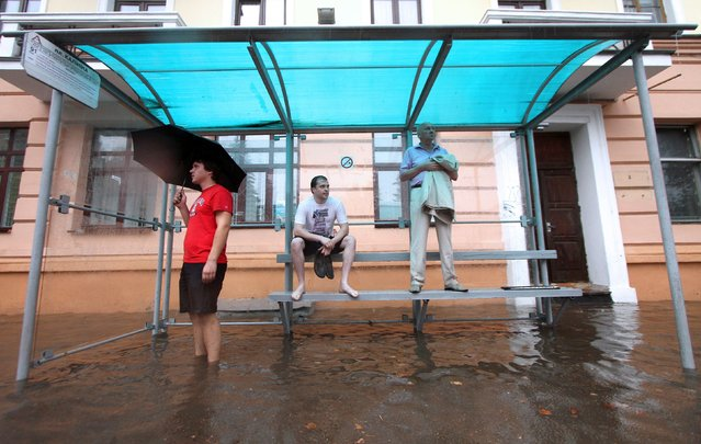 People wait for the bus in a flooded bus stop during heavy rain in Minsk, on August 12, 2014. (Photo by Sergei Gapon/AFP Photo)