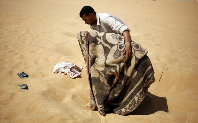 "A worker helps a patient, who is wrapped in a blanket, leave a ""sauna"" tent after his sand bath in Siwa, Egypt, August 12, 2015. In the searing heat of summer in western Egypt, at the hottest time of the day, sufferers of rheumatism, joint pain, infertility or impotence lie buried neck-deep in the sand of Siwa near Dakrour Mountain. (Photo by Asmaa Waguih/Reuters)"