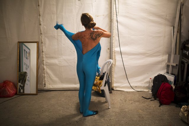 A woman wears her full solid-coloured bodysuit before taking part in a street art performance in Bat Yam, near Tel Aviv, Israel August 29, 2015. Some 40 people participated on Saturday in the performance, initiated by a group of artists called Prizma Ensemble, as part of the city's annual international street art and street theatre festival. The group says the performance deals with concepts of identity and movement in public spaces. (Photo by Amir Cohen/Reuters)