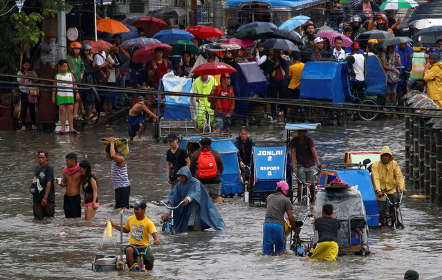 Residents wait their turn to make their way through floodwaters on pedicabs in Las Pinas, Metro Manila as a storm sweeps across the main Luzon island, Philippines, September 12, 2017. (Photo by Erik De Castro/Reuters)
