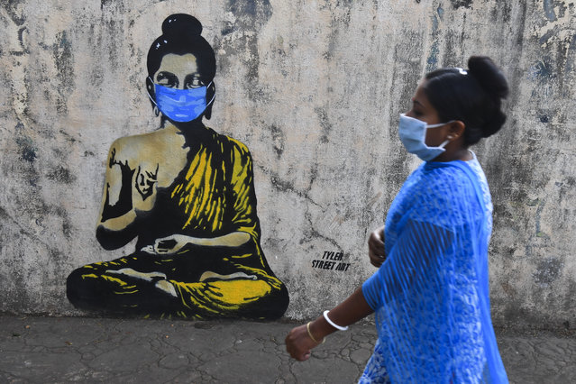 A resident wearing a facemask amid concerns over the spread of the COVID-19 novel coronavirus walks past a graffiti of Buddha wearing facemask, in Mumbai on March 16, 2020. (Photo by Indranil Mukherjee/AFP Photo)