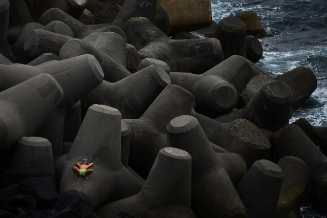 A boy rests on concrete blocks near the small port of Ginostra on June 16, 2016 on the island of Stromboli. Stromboli is part of the Aeolian Islands a volcanic archipelago in the Tyrrhenian Sea, north of Sicily. (Photo by Gabriel Bouys/AFP Photo)