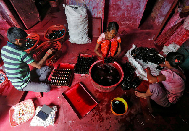 Workers fill bottles with Alta, a red dye which Hindu women apply with cotton on the border of their feet during marriages and religious festivals, at a workshop in Kolkata, India August 2, 2016. (Photo by Rupak De Chowdhuri/Reuters)