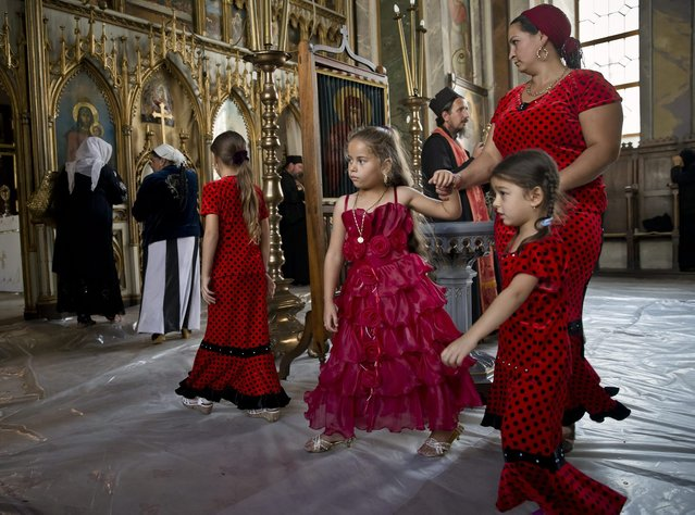 A Romanian Roma woman walks with children after a religious service celebrating the Birth of the Virgin Mary at the Bistrita Monastery in Costesti, Romania, Monday, September 8, 2014. (Photo by Vadim Ghirda/AP Photo)