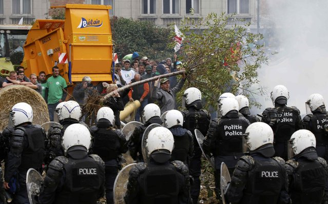 Belgian riot police officers stand guard while protesters throw a tree branch during clashes as farmers and dairy farmers from all over Europe take part in a demonstration outside an European Union farm ministers emergency meeting at the EU Council headquarters in Brussels, Belgium, September 7, 2015. (Photo by Jacky Naegelen/Reuters)