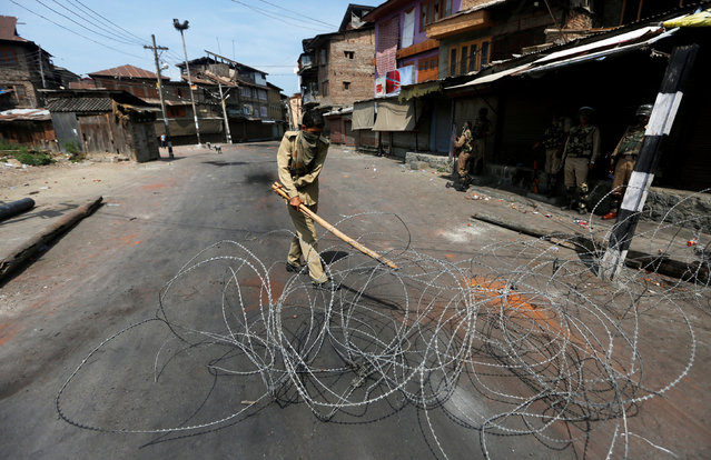 An Indian policeman uses a stick to adjust concertina wire as he lays a barricade on a road during a curfew in Srinagar, August 6, 2016. (Photo by Danish Ismail/Reuters)