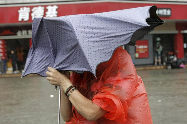 A resident holding an umbrella walks against strong winds and heavy rainfall on a flooded street as Typhoon Kalmaegi hits Haikou, Hainan province, September 16, 2014. At least two people were killed after Typhoon Kalmaegi made landfall in south China on Tuesday morning, Xinhua News Agency reported. (Photo by Reuters/China Daily)