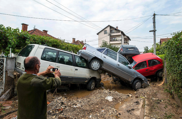 A man takes a photo of damaged vehicles following floods in the village of Stajkovci, near Skopje, on August 7, 2016. Fierce storms packing strong winds and torrential rains overnight killed at least 20 people in Macedonia's capital of Skopje, the health minister said August 7. The freak weather included winds blowing at more than 70 kilometres (43 miles) an hour and resulted in flash floods and landslides, with cars swept away by the violent torrents. (Photo by Robert Atanasovski/AFP Photo)
