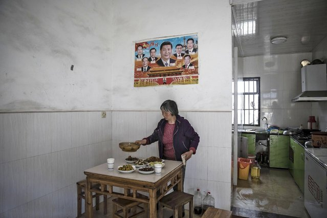 A farmer sets a table for lunch under a poster featuring Xi Jinping, China's president, and other members of the politburo standing committee at a farm which supplies fresh food to Pifu Ecological Agriculture Ltd. near Jiande, Zhejiang Province, China, on Thursday, April 6, 2017. Pifu Founder Li Xiajun leased about 7 hectares of land a decade ago to produce birds for his family and friends. He now has 666 hectares of free-range fowl that he sells direct to families as far away as Hangzhou, 100 kilometers from his farm. (Photo by Qilai Shen/Bloomberg via Getty Images)