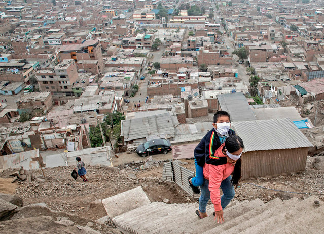 Peruvian Marlith Mori returns to her home on the heights of the Vista Alegre shantytown of the Comas district in the outskirts of Lima, carrying her impaired son Jeyson who attends daily therapy at a nearby medical facility, on May 21, 2020. Mori lives in an area where residents' low budgets force them to break mandatory isolation to find daily means of support. Peru crossed the 100 thousand confirmed cases and statistics stand as of May 21 on 108,769 infected, of which 43,587 have recovered and 3,148 have died since the virus was first detected in Peru on March 6. (Photo by Geraldo Caso/AFP Photo)