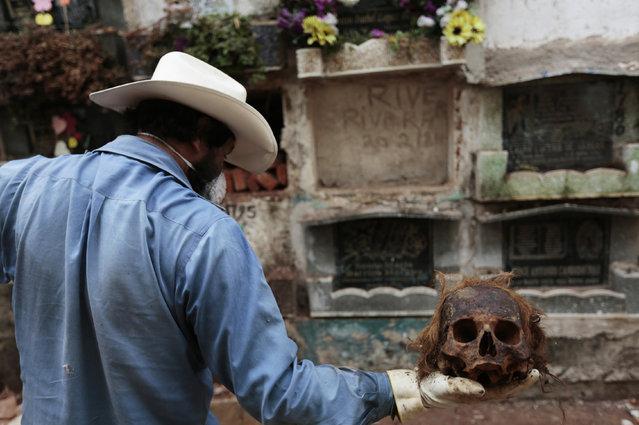 A grave cleaner holds up a skull during exhumation works at the Cemetery General in Guatemala City May 24, 2013. (Photo by Jorge Dan Lopez/Reuters)
