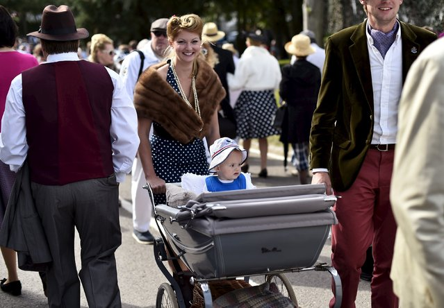 A woman pushes a child in a pram at the Goodwood Revival historic motor racing festival in Goodwood, near Chichester in south England, Britain, September 11, 2015. (Photo by Toby Melville/Reuters)