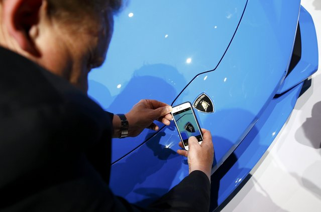 A visitor takes a picture of the logo on the Lamborghini Huracan LP 610-4 Spyder during the Volkswagen group night ahead of the Frankfurt Motor Show (IAA) in Frankfurt, Germany, September 14, 2015. (Photo by Kai Pfaffenbach/Reuters)