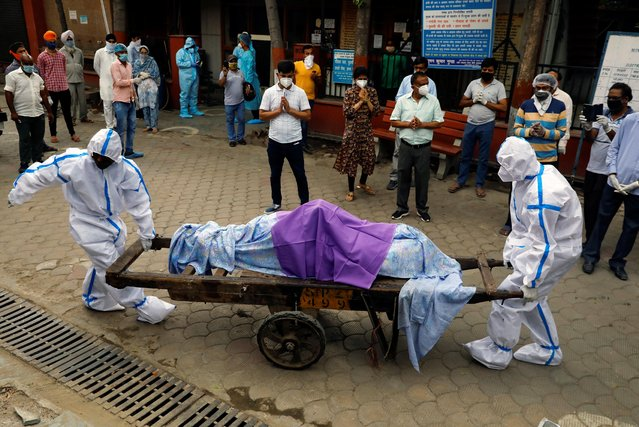 Health workers wearing Personal Protective Equipment (PPE) carry the body of a person who who died due to the coronavirus disease at a crematorium in New Delhi, India, June 24, 2020. (Photo by Anushree Fadnavis/Reuters)