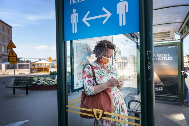 A woman wears a face mask as she waits at a bus stop with an information sign asking people to keep social distance due to the coronavirus COVID-19 pandemic on June 26, 2020 in Stockholm, Sweden. (Photo by Stina Stjernkvist/AFP Photo)