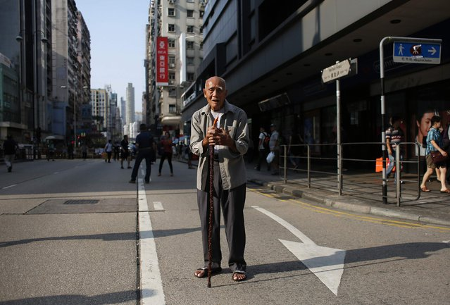 "Wong Ka-pang, 89, poses on Nathan Road in Mongkok shopping district in Hong Kong October 8, 2014. Wong, who fled mainland China in 1949, said, ""My younger brother was killed in the cultural revolution. If I don't come, who will come? I won't revolt if there is a crackdown"". (Photo by Bobby Yip/Reuters)"