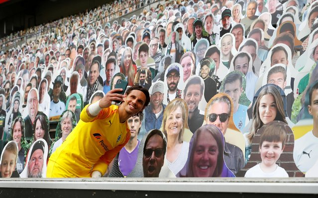 Borussia Moenchengladbach's Yann Sommer takes a selfie with the cardboard fans during their Bundesliga match in Moenchengladbach, Germany on June 27, 2020. (Photo by Wolfgang Rattay/Reuters)