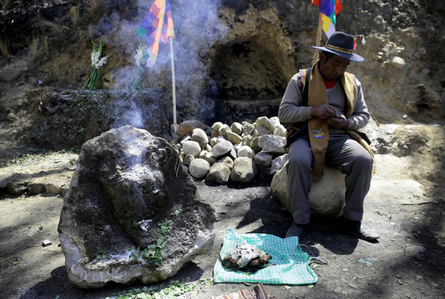 """A witch doctor rests next to a stone which bears an impression that locals refer to as """"Devil face"""", as a shrine frequented by indigenous witch doctors is cleared to expand a main highway between La Paz and El Alto, Bolivia, August 24, 2016. (Photo by David Mercado/Reuters)"""