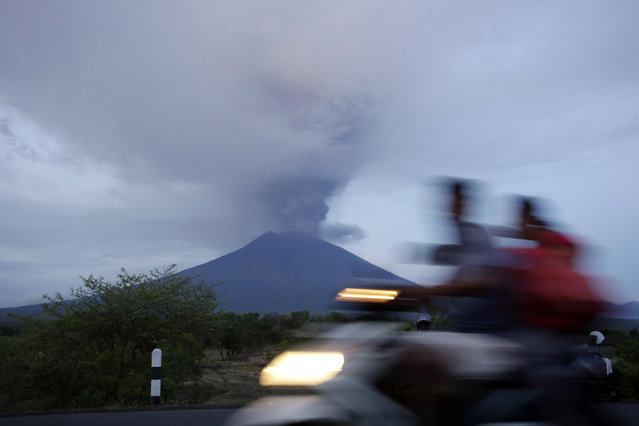 A motorcyclist passes by the Mount Agung volcano erupting in the background in Karangasem, Indonesia, Monday, November 27, 2017. (Photo by Firdia Lisnawati/AP Photo)