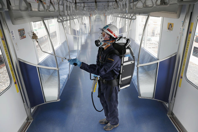 A Tokyo Metro worker, wearing goggle and protective mask, sprays chemicals to make anti-virus coating inside a passenger car at its depot Thursday, July 9, 2020, in Tokyo. The subway company plans to disinfect all 2720 cars by mid August this year, Kyodo News reported.  Japan lifted a seven-week pandemic state emergency in late May, and social and business activity have since largely resumed. (Photo by Kyodo News via AP Photo)