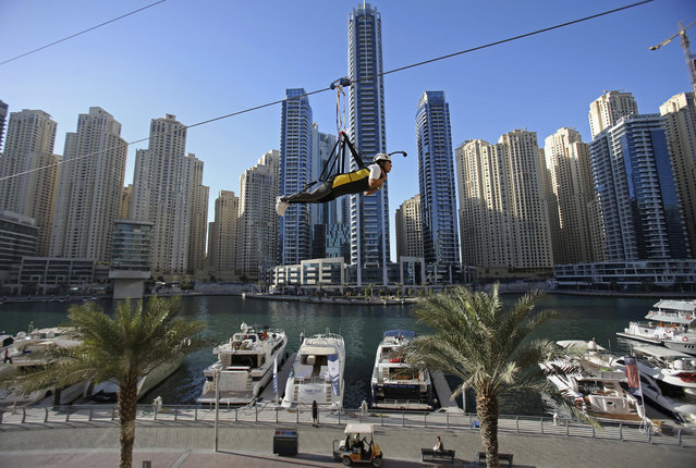 A woman rides the world's longest urban zip line, with a speed of up to 80 kilometers per hour on a one kilometer run from 170 meter to ground level, in the Marina district of Dubai, United Arab Emirates, Tuesday, December 5, 2017. (Photo by Kamran Jebreili/AP Photo)