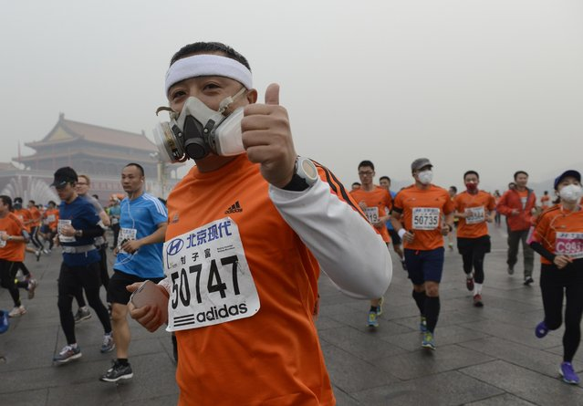 Participants wearing masks during a hazy day at the Beijing International Marathon in front of Tiananmen Square, in Beijing, October 19, 2014. (Photo by Reuters/Stringer)