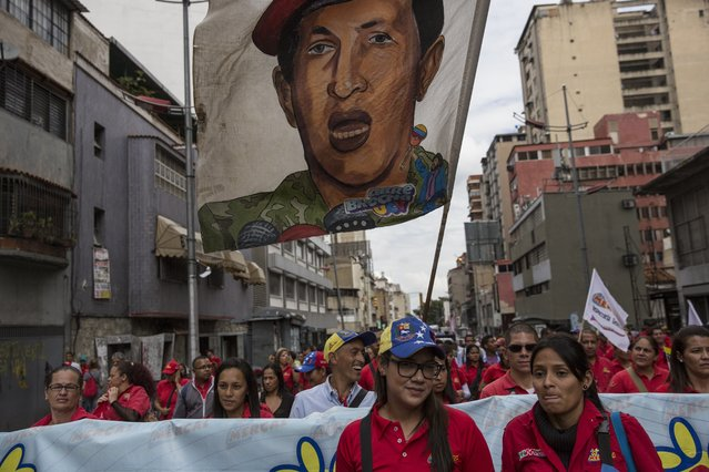 People march with a banner of Venezuela's late former president Hugo Chavez, in support of President Nicolas Maduro, in downtown in Caracas, Venezuela, Wednesday, October 25, 2017. (Photo by Rodrigo Abd/AP Photo)