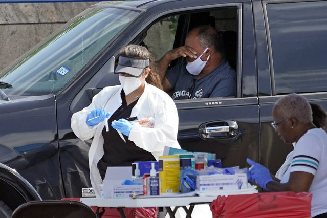 A patient reacts after a healthcare worker collected a sample at a United Memorial Medical Center COVID-19 testing site Thursday, July 16, 2020, in Houston. (Photo by David J. Phillip/AP Photo)