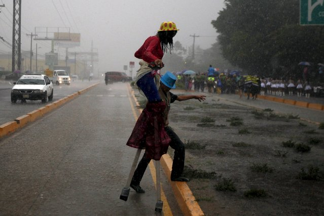 A man helps a woman on stilts to cross the street after celebrations for the 437th anniversary of the city of Tegucigalpa was suspended due to heavy rains in Tegucigalpa, September 26, 2015. (Photo by Jorge Cabrera/Reuters)
