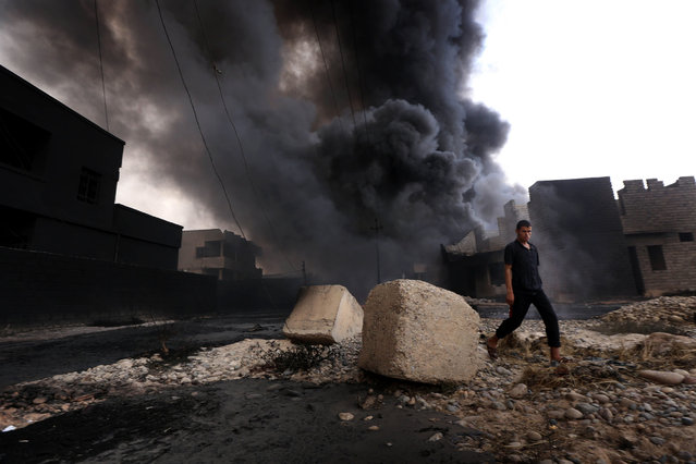 An Iraqi man walks near smoke billowing from oil wells, set ablaze by Islamic State (IS) group militants before fleeing the oil-producing region of Qayyarah, on August 30, 2016, after Iraqi forces pushed the jihadists out of the northern town on the banks of the Tigris river. Iraqi forces on August 25 retook key areas in the city and pushed the Islamic State group from Qayyarah, a northern town considered strategic for any future offensive against the jihadists' last stronghold of Mosul. (Photo by Safin Hamed/AFP Photo)