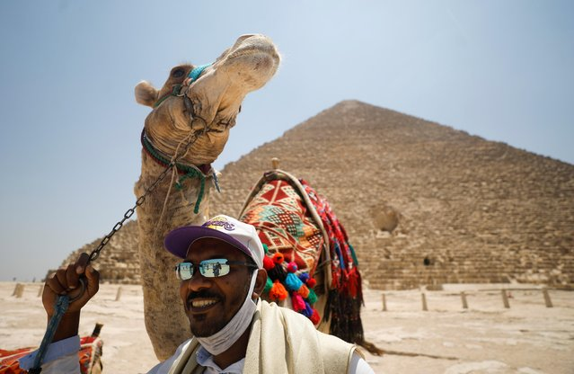 A man with a camel is seen in front of the Great Pyramids of Giza after reopening for tourist visits, following the outbreak of the coronavirus disease (COVID-19), in Cairo, Egypt on July 1, 2020. (Photo by Mohamed Abd El Ghany/Reuters)