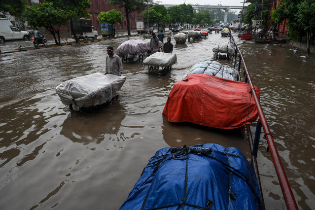 Street vendors pull their carts protected with tarpaulin as they wade through a flooded street after heavy monsoon rains in Lahore on July 16, 2020. (Photo by Arif Ali/AFP Photo)