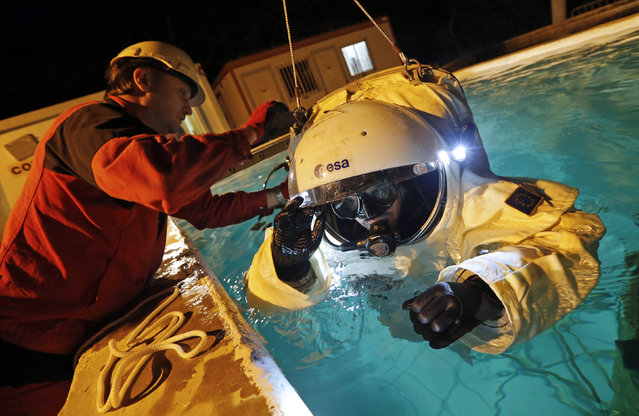 Comex Space division manager Peter Weiss (L) checks the Gandolfi space suit of National Diving School director Jerome Vincent (R) during a training session in a swimming pool in Marseille October 22, 2014. (Photo by Jean-Paul Pelissier/Reuters)