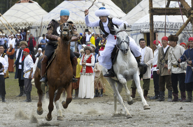 In this photo taken on Sunday, September 4, 2016, participants take part in a horse-riding competition during the second World Nomad Games at Issyk Kul lake in Cholpon-Ata, Kyrgyzstan. The Games, which opened on Saturday on a picturesque mountain plain in eastern Kyrgyzstan, bring together athletes from 40 countries including Russia and the United States where nomadic traditions are strong. (Photo by Vladimir Voronin/AP Photo)