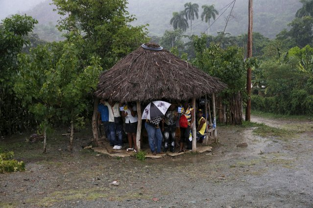 People take refuge from the rain under a hut after Pope Francis drove past in El Cobre, Cuba, September 21, 2015. (Photo by Carlos Garcia Rawlins/Reuters)