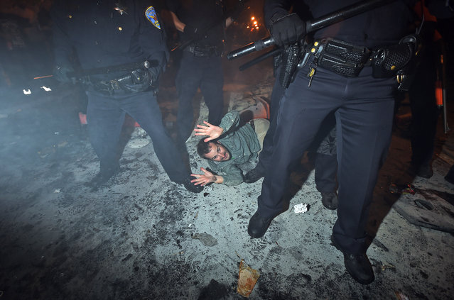 San Francisco police officers subdue a man who was seen driving a meter maid vehicle through the Mission district after the San Francisco Giants won the World Series baseball game against the Kansas City Royals on Wednesday, October 29, 2014, in San Francisco. (Photo by Noah Berger/AP Photo)
