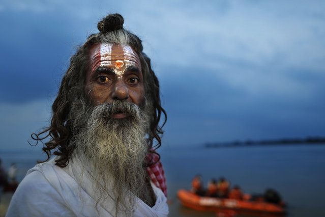 A Hindu holy man looks at a decoration on the ghats of the river Saryu as part of preparations for the groundbreaking ceremony of a temple to the Hindu god Ram in Ayodhya, in the Indian state of Uttar Pradesh, Monday, August 3, 2020. As Hindus prepare to celebrate the groundbreaking of a long-awaited temple at a disputed ground in northern India, Muslims say they have no firm plans yet to build a new mosque at an alternative site they were granted to replace the one torn down by Hindu hard-liners decades ago. (Photo by Rajesh Kumar Singh/AP Photo)