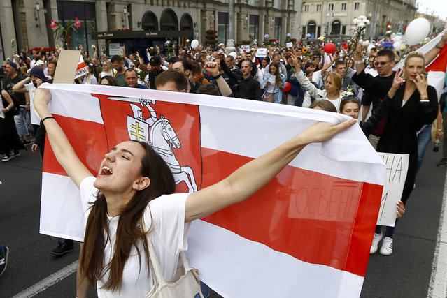A woman reacts as she marches holding an old Belarusian national flag in the center of Minsk, Belarus, Friday, August 14, 2020. Some thousands of people have flooded the cnetre of the Belarus capital, Minsk, in a show of anger over a brutal police crackdown this week on peaceful protesters that followed a disputed election. (Photo by Sergei Grits/AP Photo)