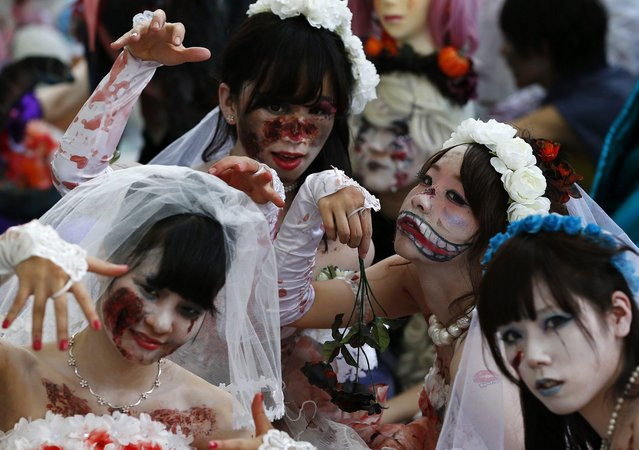 Participants in costumes pose for pictures after a Halloween parade in Kawasaki, south of Tokyo, October 26, 2014. More than 100,000 spectators turned up to watch the parade, where 2,500 participants dressed up in costumes, according to the organiser. (Photo by Yuya Shino/Reuters)