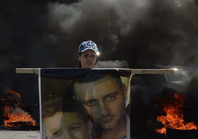 A relative of Lebanese soldier, who was kidnapped by Islamic State (IS) and the Nusra Front (JAN) since August 2014, carries his picture as she stands next to burnt tires during a protest at the Rafik Hariri international airport highway, Beirut, Lebanon, 04 October 2015. Relatives of kidnapped Lebanese soldiers are calling on the government to take action to secure the release of the captives. (Photo by Wael Hamzeh/EPA)