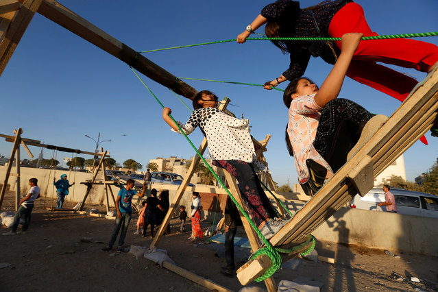 Children play on a handmade swings, during the first day of the Muslim holiday Eid al-Adha in Amman, Jordan September 12, 2016. (Photo by Muhammad Hamed/Reuters)