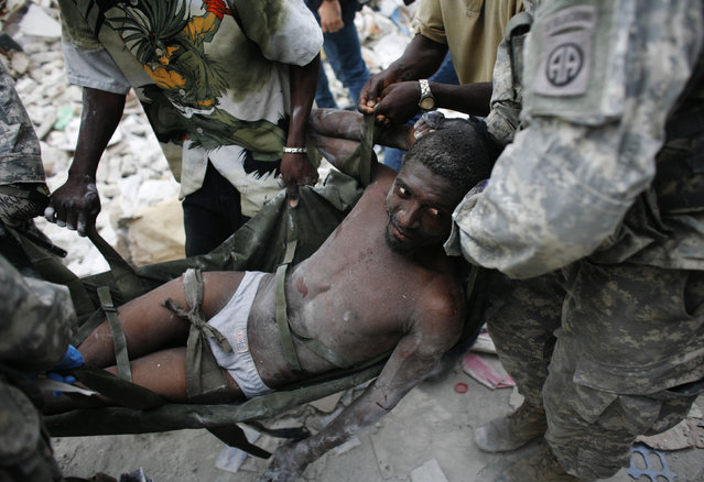 Rico Dibrivell, 35, is attended by a U.S. military rescue team after being freed from the rubble of a building in Port-au-Prince, Haiti, January 26, 2010. (Photo by Eduardo Munoz/Reuters)