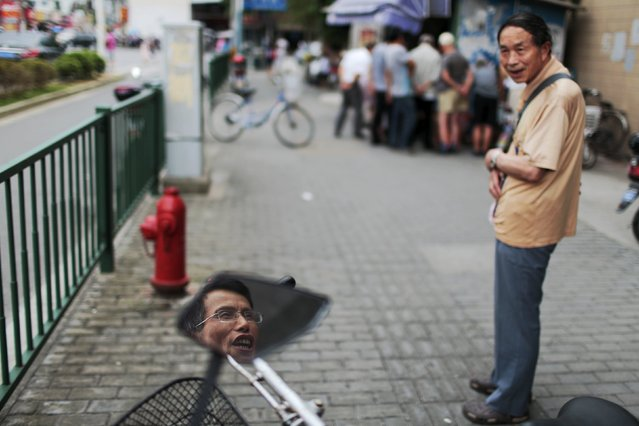 Du Mingpeng's face is seen reflected on his electric bike's rearview mirror, as he talks to his friend outside a brokerage house in Shanghai, China, July 22, 2015. Du Mingpeng, 50, is a jewellerystore security guard and investor who started trading stocks because he wanted to make some more money for his family, on top of his salary. With 30,000 yuan as his capital, he has made 160,000 yuan from trading stocks. Now even though the market doesn't look great, he still believes with his experience he won't lose money. (Photo by Aly Song/Reuters)