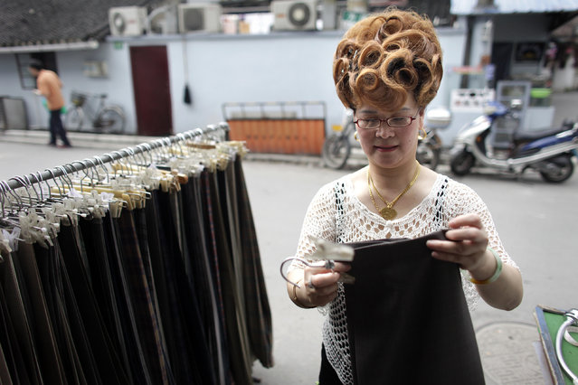 Shop owner Gong Chui Zhen fixes trousers at the entrance to her shop in an old quarter of Shanghai. (Photo by Nir Elias/Reuters)
