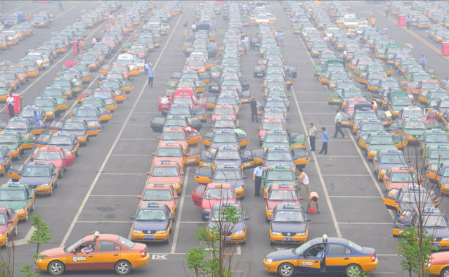 Taxi drivers wait for passengers at the Beijing Railway Station on February 5, 2006 in Beijing, China. (Photo by China Photos/Getty Images)
