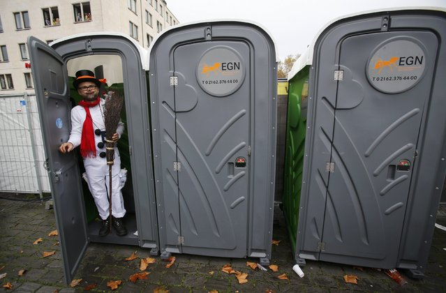 A carnival reveller stands in a plastic toilet cabin during the start of the carnival season in Cologne November 11, 2014. In many parts of Germany, at 11:11am on November 11, people mark the official start of carnival, a season of controlled raucous fun that reaches a climax during the days before Ash Wednesday and the start of Lent. (Photo by Wolfgang Rattay/Reuters)