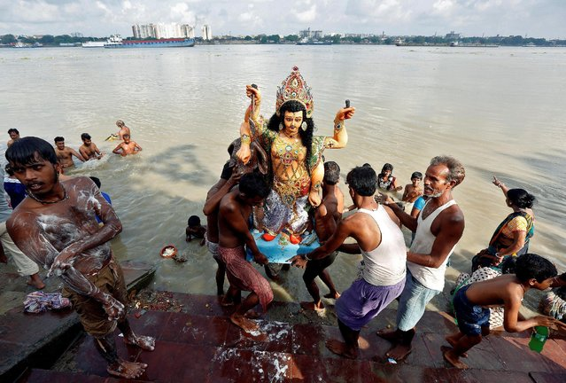 Devotees carry an idol of Lord Vishwakarma, the Hindu deity of architecture and machinery, to immerse it into the waters of the river Ganga in Kolkata, India, September 19, 2016. (Photo by Rupak De Chowdhuri/Reuters)