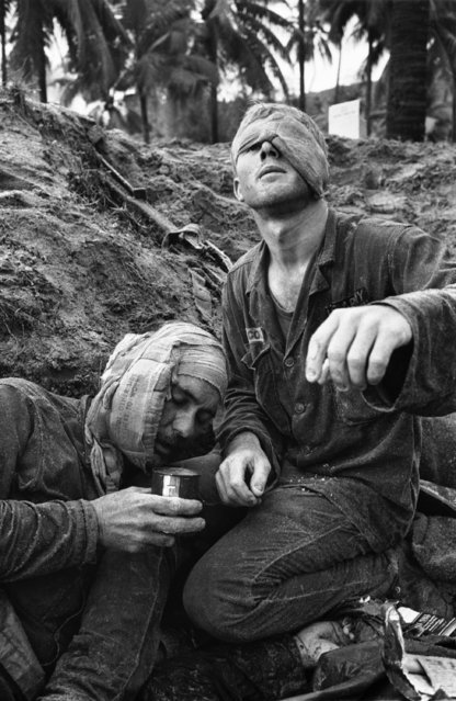 First Cavalry Division medic Thomas Cole, of Richmond, Va., right, with one of his own eyes bandaged, continues to treat wounded Staff Sgt. Harrison Pell, of Hazleton, Pa., during a January 30, 1966 firefight at An Thi in the Central Highlands between U.S. troops and a combined North Vietnamese and Vietcong force. (Photo by Henri Huet/AP Photo)